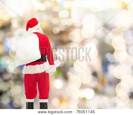 christmas, holidays and people concept - man in costume of santa claus with bag from back over lights background