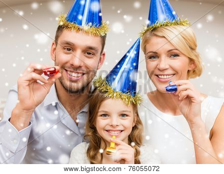 celebration, family, holidays and birthday concept - happy family wearing blue party hats and blowing favor horns at home