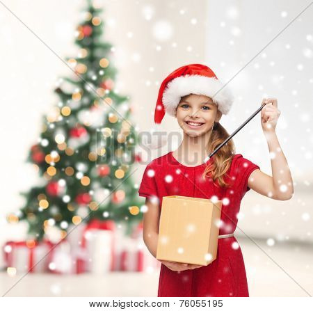holidays, childhood and people concept - smiling girl in santa helper hat with gift box, magic wand over living room and christmas tree background