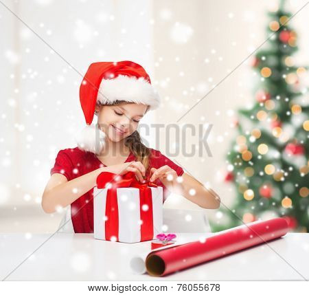 childhood, decorating and people concept- smiling girl in santa helper hat with gift box, wrapping paper over living room with christmas tree and snow background