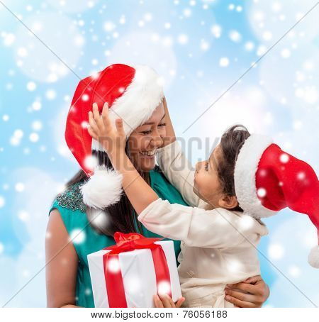 christmas, holidays, celebration, family and people concept - happy mother and child girl in santa helper hats with gift box over blue lights background
