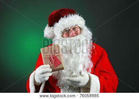 Santa Claus holds a Christmas Present for You the Viewer. Santa Claus aka Chris Kringle, Old Man Winter, Saint Nick, Jolly Old Elf, Man in Red Velvet, Santa, and many other names is loved by everyone