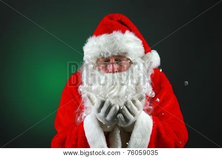 Santa Claus wears his eye glasses and blows snow while looking into the camera. Santa Claus loves Christmas and Snow and all things magical.  Christmas is a Magical Time of the year.