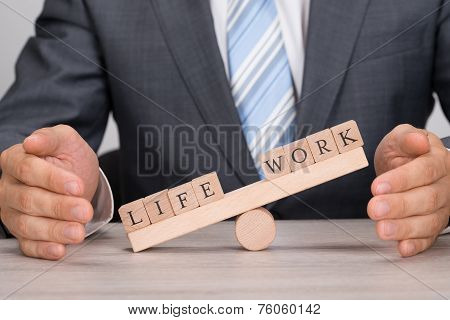 Businessman Covering Imbalance Between Life And Work On Seesaw