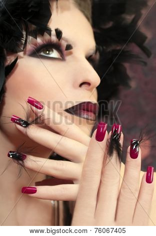 Burgundy manicure with feathers.