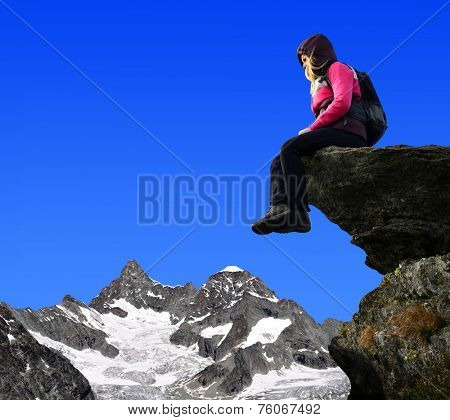 Girl sitting on a rock, in the background mount Ober Gabelhorn - Swiss Alps, Europe