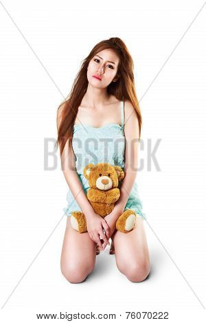 Teenage girl holding her teddybear isolated over white