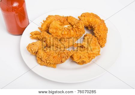 Chicken Strips On White Plate With Hot Sauce On Side