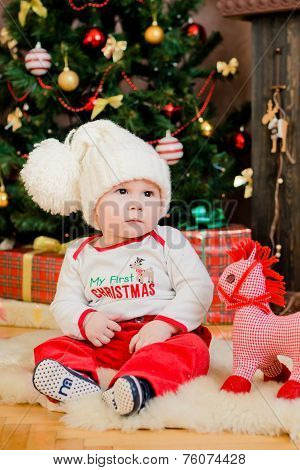 Toddler Sitting In A Christmas Interior