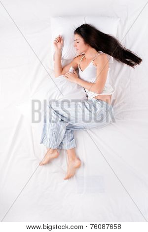 Woman sleeping in open fetal position with pillow