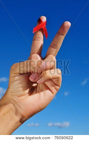 a man hand doing the V sign with a red awareness ribbon for the fight against AIDS