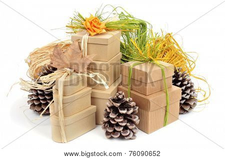 some gift boxes tied with natural raffia of different colors and surronded by natural ornaments such as pinecones on a white background