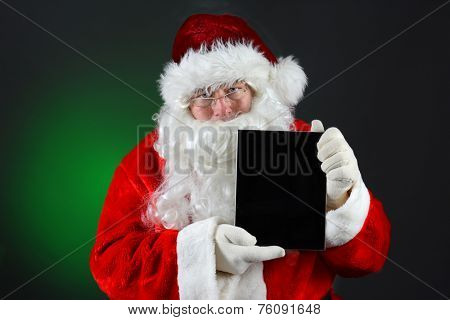 Santa Claus holding a tablet computer with its blank screen facing the viewer in vertical orientation. Horizontal image on a light to dark green background.
