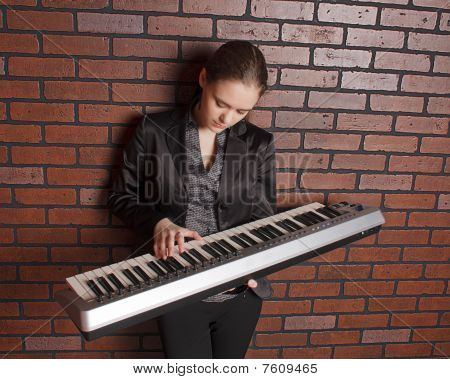Portrait Of Musician With Synthesizer Near Brick Wall
