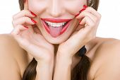stock photo of crooked teeth  - Beautiful smiling girl with retainer for teeth and with red lipstick sticking her tongue out close - JPG