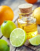 stock photo of essential oil  - citrus essential oil and slice of orange lemon and lime fruits on old wooden table - JPG