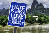 picture of hate  - Hate is Easy Love Takes Courage sign with a forest background - JPG