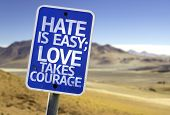 image of hate  - Hate is Easy Love Takes Courage sign with a desert background - JPG