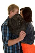 picture of sneak  - a man and woman sneaking a kiss behind a hat - JPG