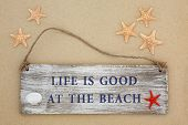 foto of cockle shell  - Life is good at the beach sign with starfish and cockle shell on sand background - JPG