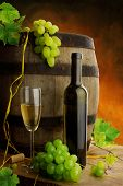 image of wine bottle  - White wine still life with wine barrel and grapes with fresh leaves - JPG