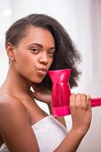 foto of dark-skin  - Beautiful  dark skinned girl blowing  dry her  hair with rose hairdryer  isolated on white background with Cupid  bow and singing looking at camera - JPG