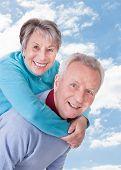 stock photo of piggyback ride  - Portrait of happy senior man giving piggyback ride to woman against sky - JPG