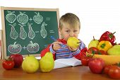 pic of role model  - funny kid on math lesson with fruits and vegetables