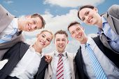 picture of huddle  - Low angle portrait of happy businesspeople making huddle against cloudy sky - JPG