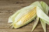 stock photo of corn cob close-up  - Close-up of a corn on the cob with leaf on a wood