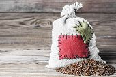 stock photo of thrift store  - Concept of the thrift storing - Red rice in the burlap sack with the patch on a wooden background