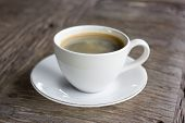 image of cozy hearth  - Cup of hot coffee on a wooden table in cafe - JPG