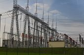 picture of substation  - Electric substation, cloudy sky, green grass, large transformers