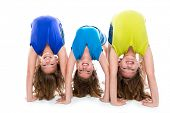 stock photo of three sisters  - twin kid sisters girls friends playing as flexible contortionist happy on white background - JPG