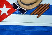 stock photo of panama hat  - Cigars straw Panama hat and sun glasses on painted background - JPG
