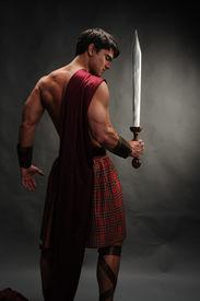 foto of sword  - the muscular highlander stands holding a sword - JPG