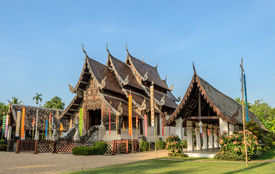 stock photo of woodcarving  - Ancient wooden teak temple of Lanna architecture with fine woodcarvings and gilded stuccos - JPG