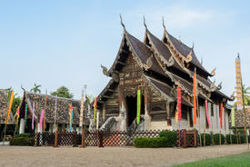 foto of woodcarving  - Ancient wooden teak temple of Lanna architecture with fine woodcarvings and gilded stuccos - JPG
