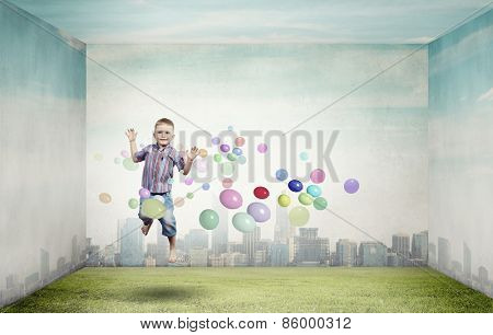Little cute boy in jump and colorful balloons around