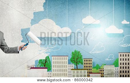 Close up of businessman hand painting wall with roller