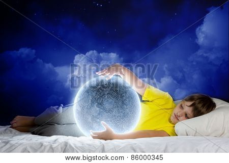 Cute boy sleeping in bed with moon