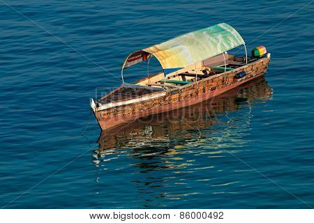 Anchored wooden boat with reflection in water, Zanzibar island