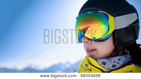 Woman wearing a helmet and glasses on the background of snow mountains.