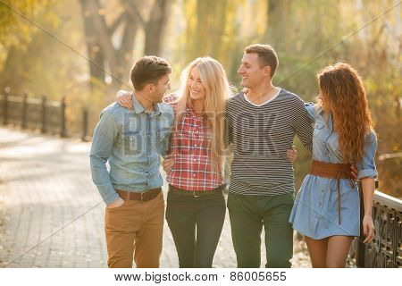 Four good friends relax and have fun in autumn park.