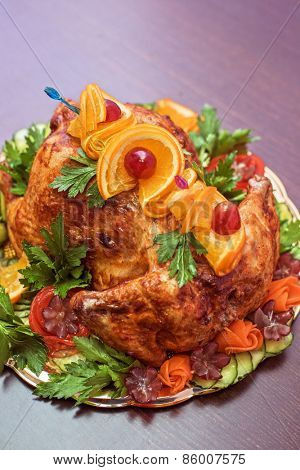 Whole roasted chicken with vegetables and fruits on wooden table