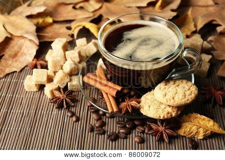 Glass cup of coffee, tasty cookies and autumn leaves on wooden background