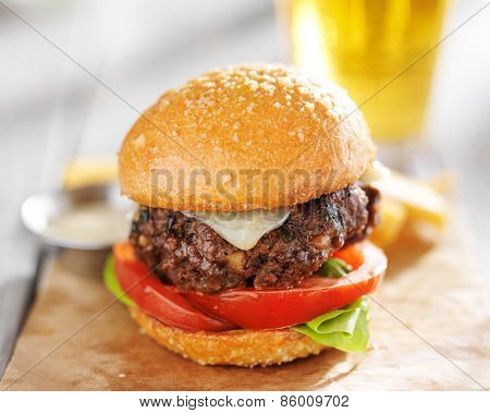 burger with beer and fries served on wax paper