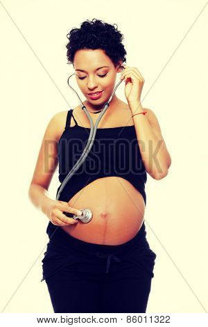Pregnant  woman with stethoscope listening to baby.