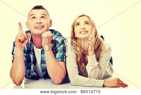 Happy couple look on empty copy space