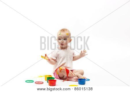 Surprised Child Soiled By Multi-colored Paints Sits On A White Background